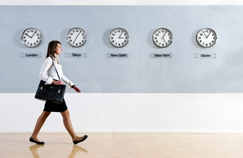 Business woman walking hurrily past a row of clocks showing the time in various parts of the world. Business, travel, time concept